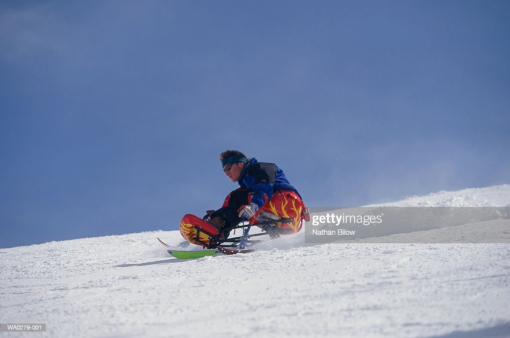 Man using sit-ski, leaning into slope, balancing on outriggers