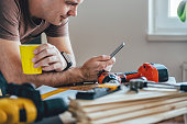 Man using smart phone and holding yellow cup of coffee in front of table with tools at home