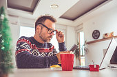Man wearing blue sweater and eyeglasses using smart phone at home during christmas holidays