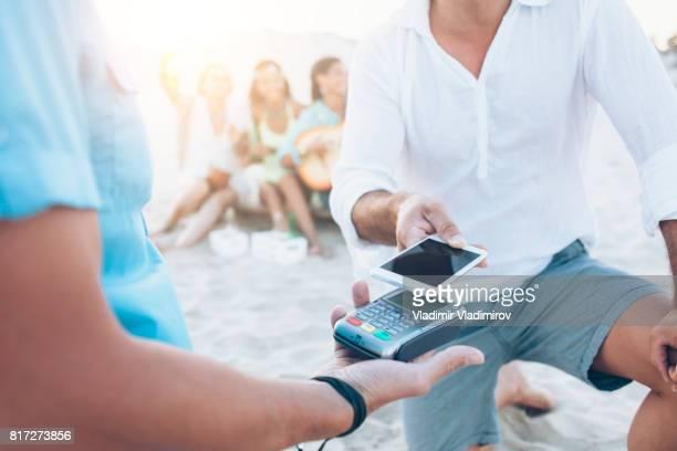 Hombre usando el teléfono inteligente para pago sin contacto en la playa