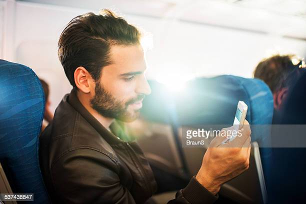 Man using smart phone in airplane.