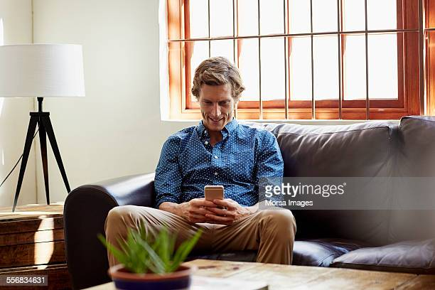 Man using smart phone on sofa at home