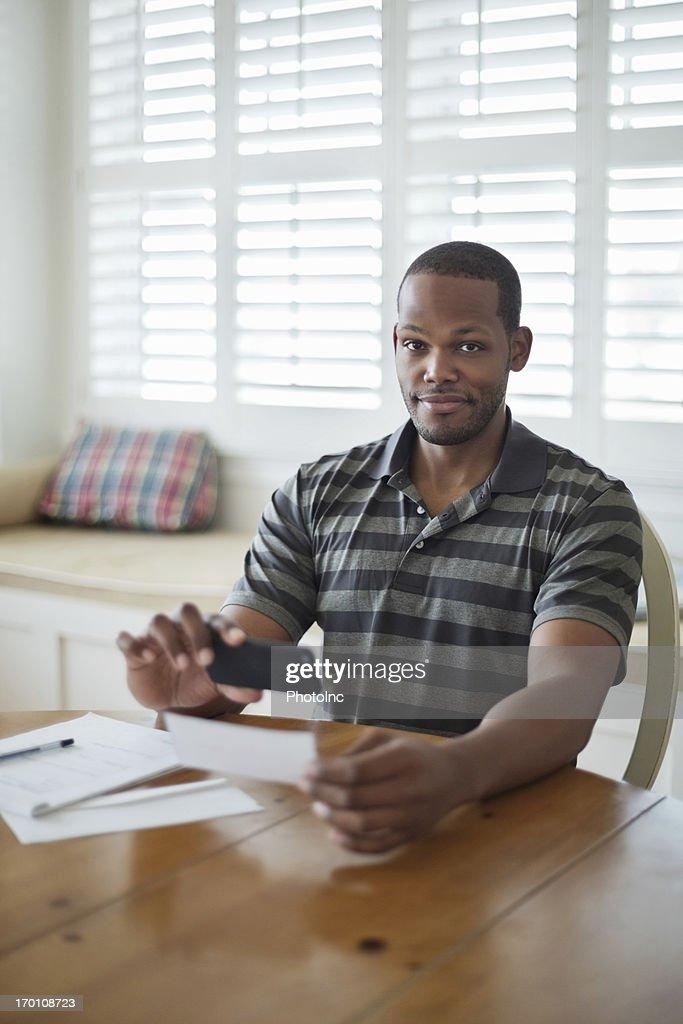 Man Using Smart Phone To Deposit Bank Slip At Table