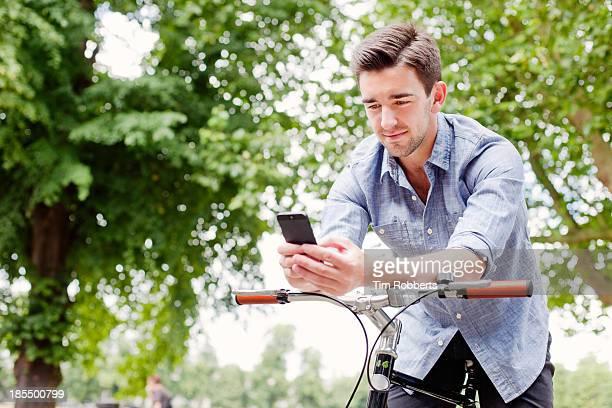 Man using smart phone whistle on bike.