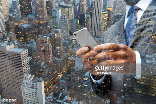 Man using smart phone with buildings