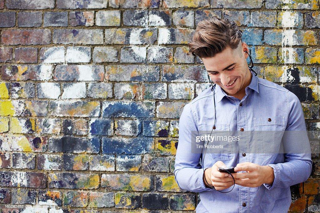 Man using smart phone with headphones. : Stock Photo