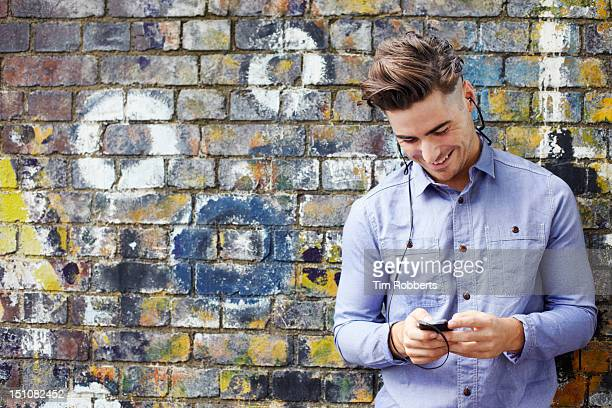 Man using smart phone with headphones.