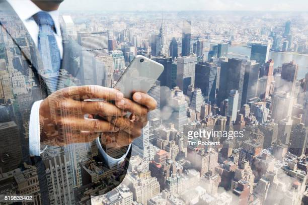 Man using smart phone with New York buildings