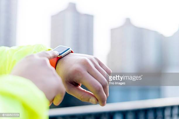 man using smart watch outdoors after jogging