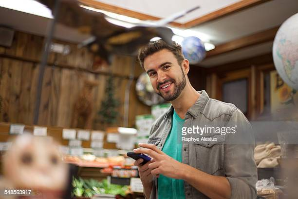 Man using smartphone in health food store