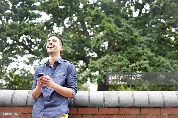 Man using smartphone leaning on low wall.