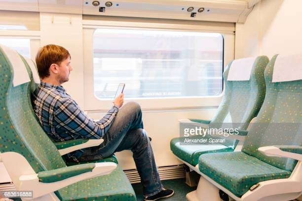Man using smartphone on a high speed train