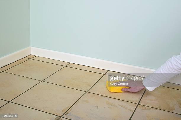 Man using sponge to clean grout off tiled floor in room
