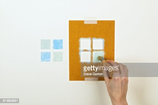 Man using stencil and paintbrush to create pattern on wall