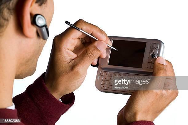 Man Using Stylus on PDA and Wireless Phone