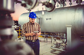 Man wearing blue hardhat using tablet at Natural gas processing facility