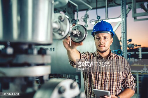 Man using tablet at Natural gas processing facility : Stock Photo