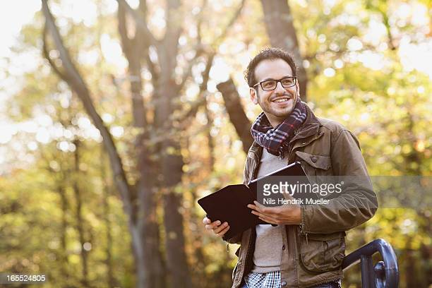 Man using tablet computer in forest
