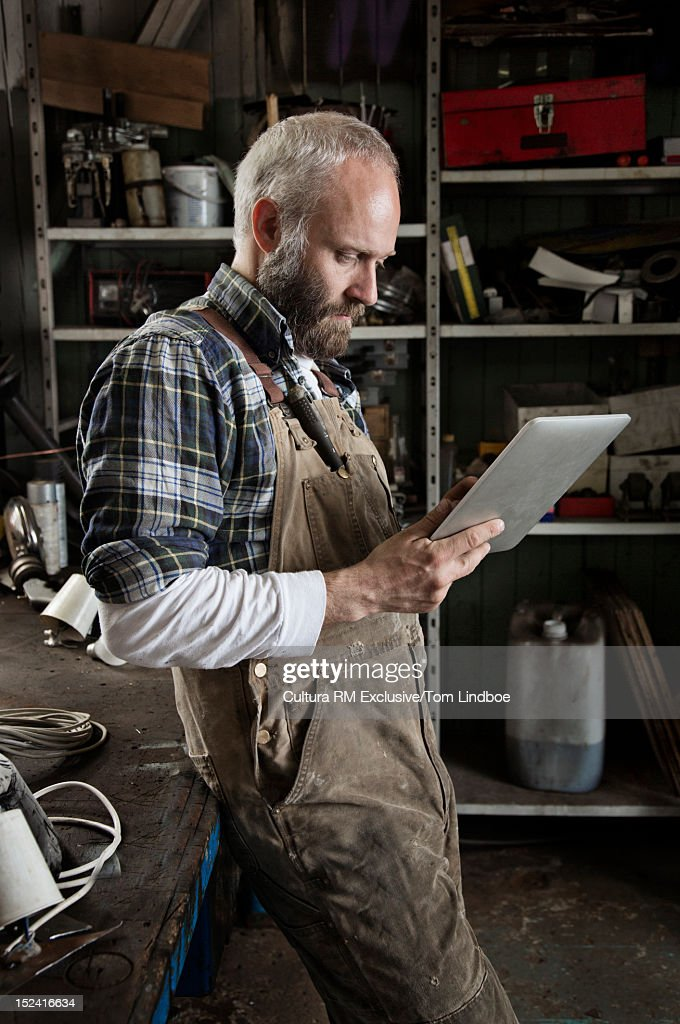 Man using tablet computer in workshop : Stock Photo