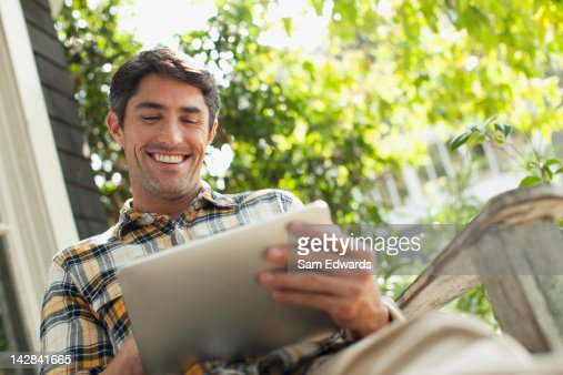 Man using tablet computer outdoors : Stock Photo