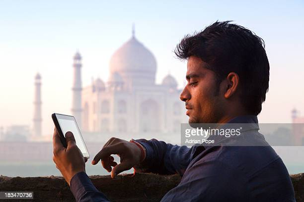 Man using tablet device with Taj Mahal beyond