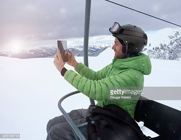 Man using tablet on ski lift.