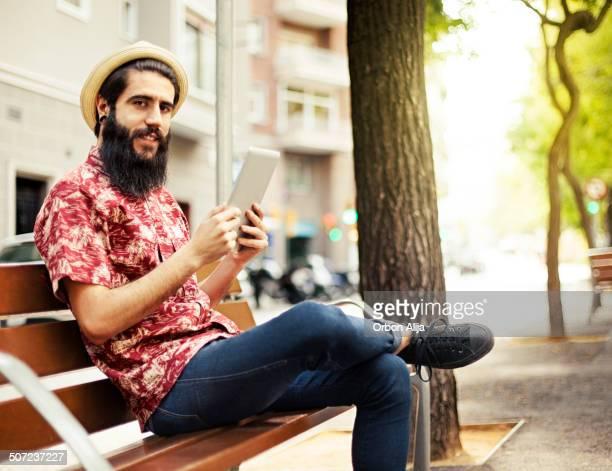 Homme à l'aide de la tablette à l'extérieur