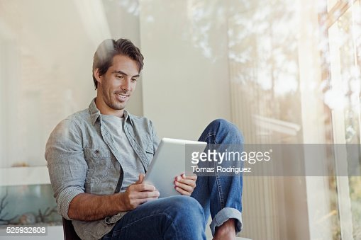 Man using tablet pc at home : Stock Photo