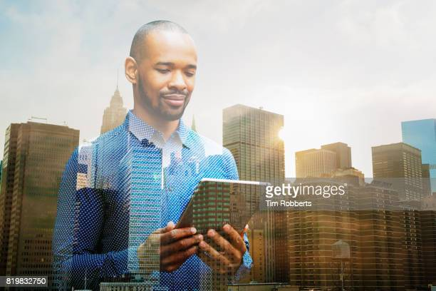 Man using tablet with buildings.