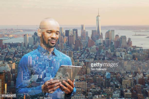 Man using tablet with Manhattan view, New York