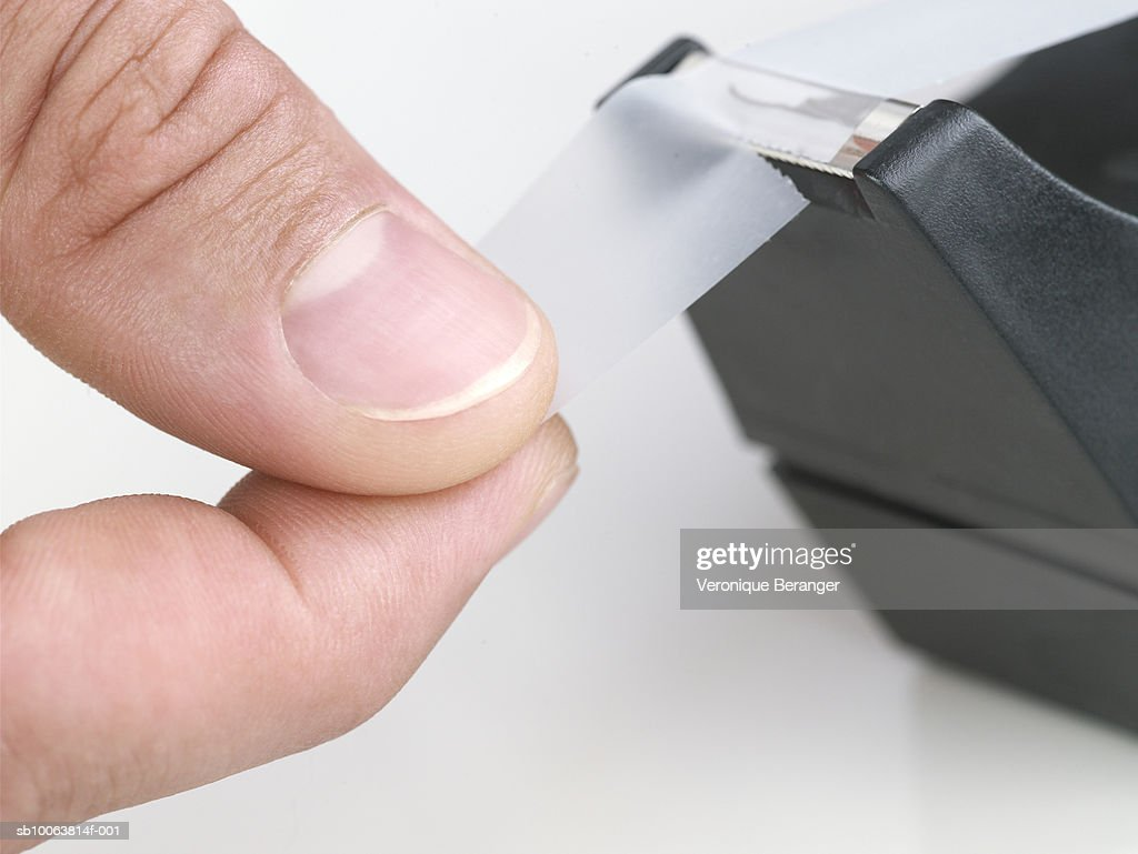 Man using tape dispenser, close-up : Stock Photo