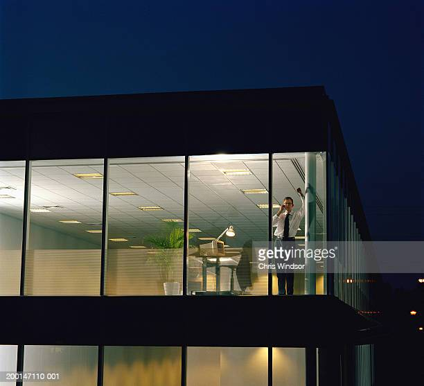 Man using telephone in office, view through window, night