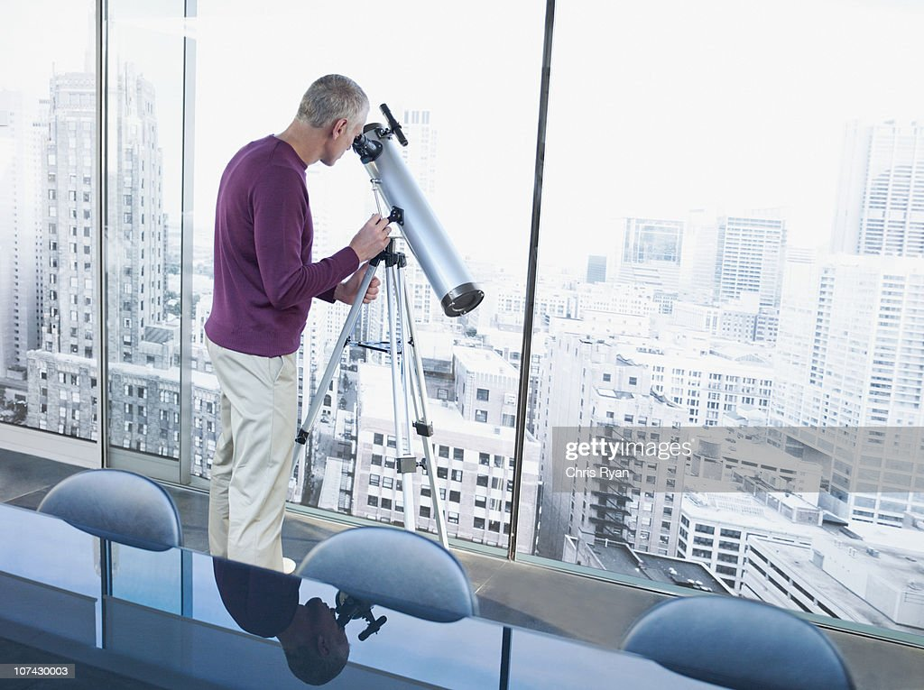 Man using telescope to look at city buildings : Stock Photo