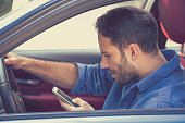 Portrait of handsome young business man using texting on mobile phone while driving a car
