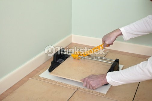 Man Using Tile Cutter To Accurately Cut Floor Tile Stock Photo