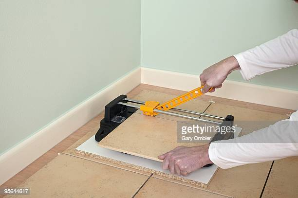Man using tile cutter to accurately cut floor tile