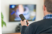 Man holding a Television remote control, changing channels, selective focus on the foreground with TV on in the background.