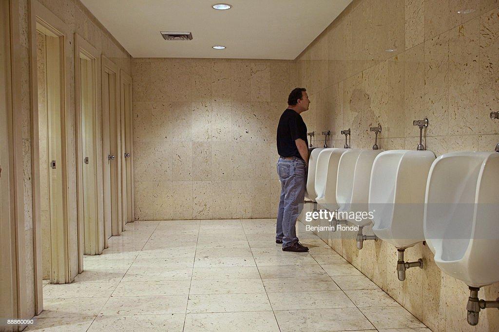 Man using urinal in public bathroom