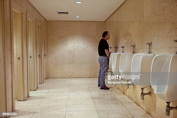 Man using urinal in public bathroom