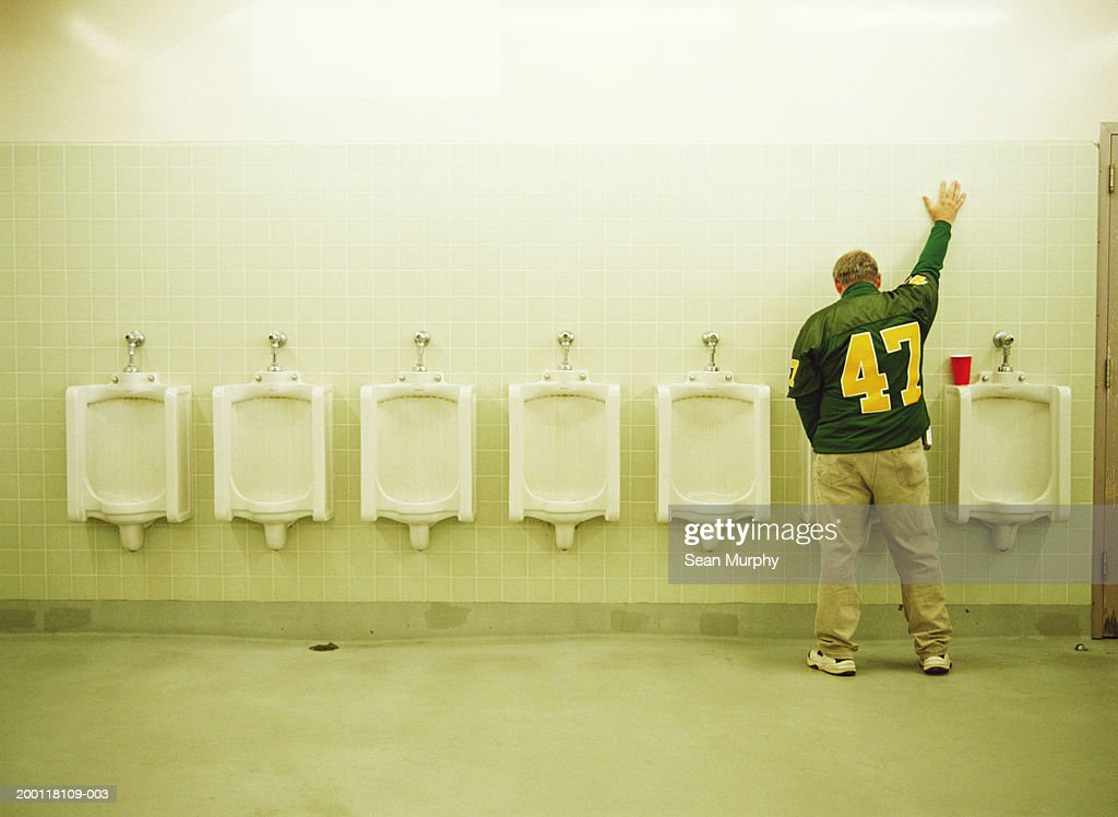 Man using urinal, one hand up on tile wall