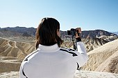 Man using video camera in desert (rear view), Death Valley, California, USA