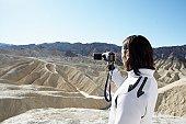 Man using video camera in desert, Death Valley, California, USA