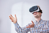Happy man in checkered shirt using virtual reality headset in white room