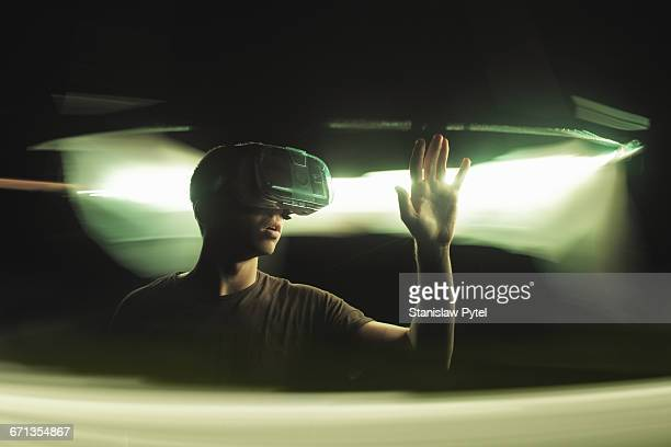 Man using VR goggles, touching light