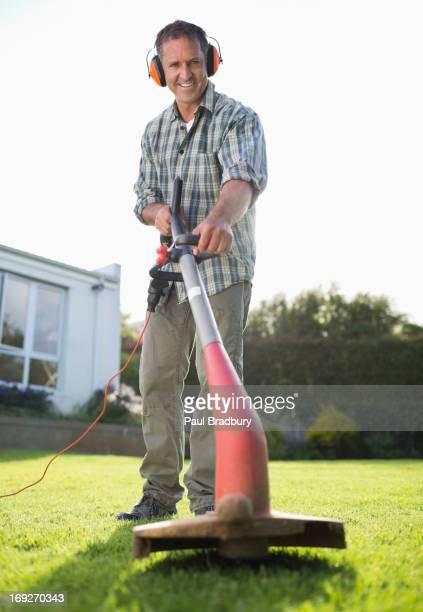 Man using weed whacker in backyard