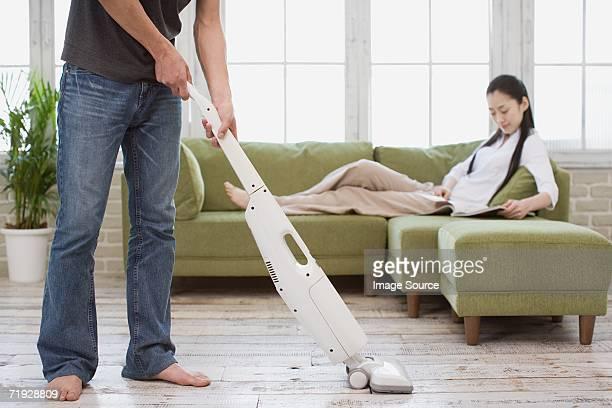 Man vacuuming and woman reading a magazine