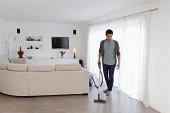 Man vacuuming living room floor