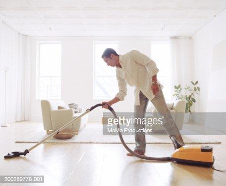 Man vacuuming living room floor, side view : Stockfoto