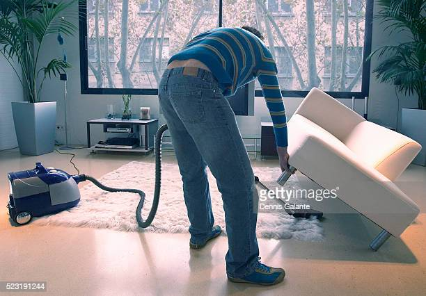 Man Vacuuming Under Couch