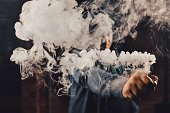 Vaping man wearing a hat, holding up a mod, obscured behind a cloud of vapor. Processed with VSCO c2 preset